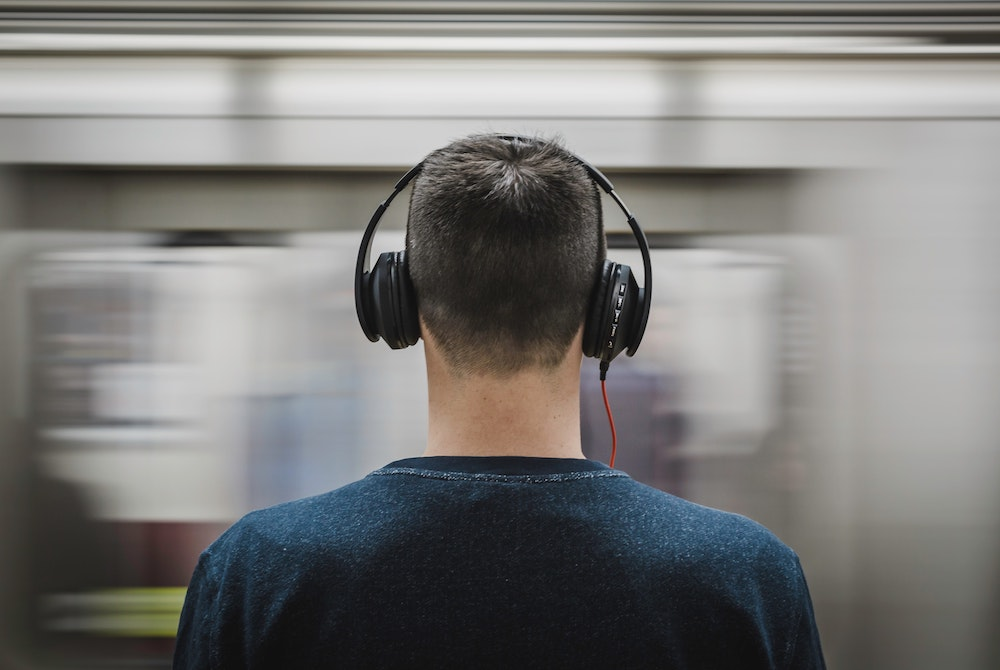 Man looking passing train and wearing headphones